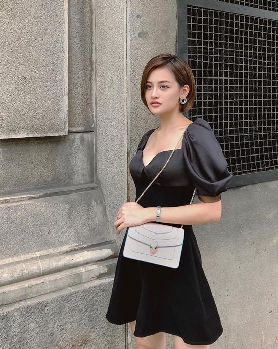 Thùy Anh thanh lịch với mốt váy tay bồng thiết kế trên chất liệu lụa đen. Phụ kiện đi kèm là túi BVLGari tông màu tương phản.