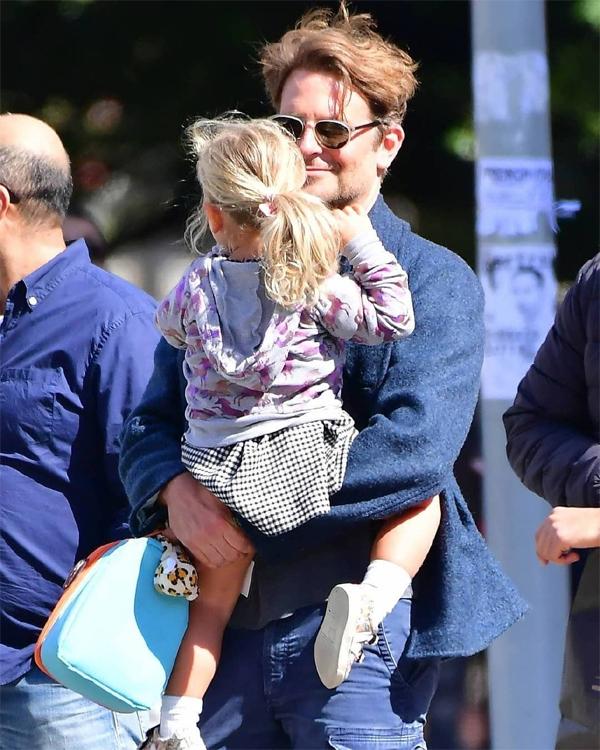 Bradley Cooper ôm con gái trong lòng, tay xách theo chiếc túi xinh xắn của cô bé 2 tuổi rưỡi.