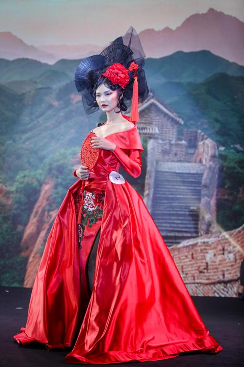 Thí sinh Nguyễn Hùng Khang biến hóa người mẫu Rosa Vũ thành thiếu nữ Trung Quốc với đôi môi đỏ, kiểu vẻ mắt sắc và tóc bới cầu kỳ, thêm điểm nhấn là bộ váy tông đỏ với hình ảnh bông hoa.