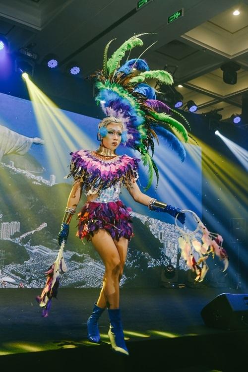 DragQueen Pia chọn trang phục Brazail - đất nước nổi tiếng về giải trí, lễ hội Carnival và những điệu nhảy hạnh phúc. Lối trang điểm nhấn vào phần mắt ngập sắc màu và bộ cánh lông lộng lẫy.