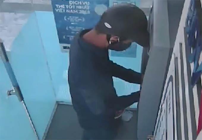 Người bịt mặt đang cài thiết bị để đánh cắp dữ liệu ở cây ATM. Ảnh: Cắt từ video