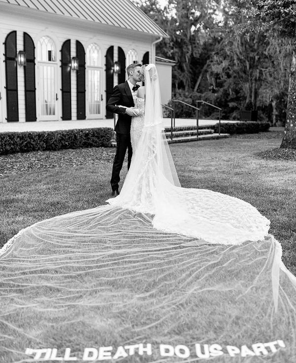 Cặp đôi chụp hình với concept cổ điển bên căn nhà xinh xắn tại resort. Hailey đội voan dài in dòng chữ Chỉ cái chết mới chia lìa được đôi ta.