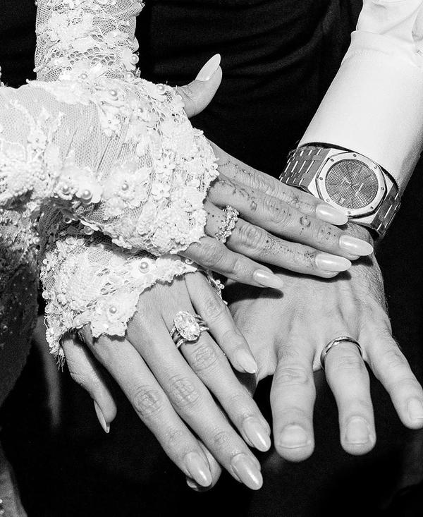 Cô dâu - chú rể tay chạm tay khoe nhẫn cưới và nhẫn đính hôn kim cương.