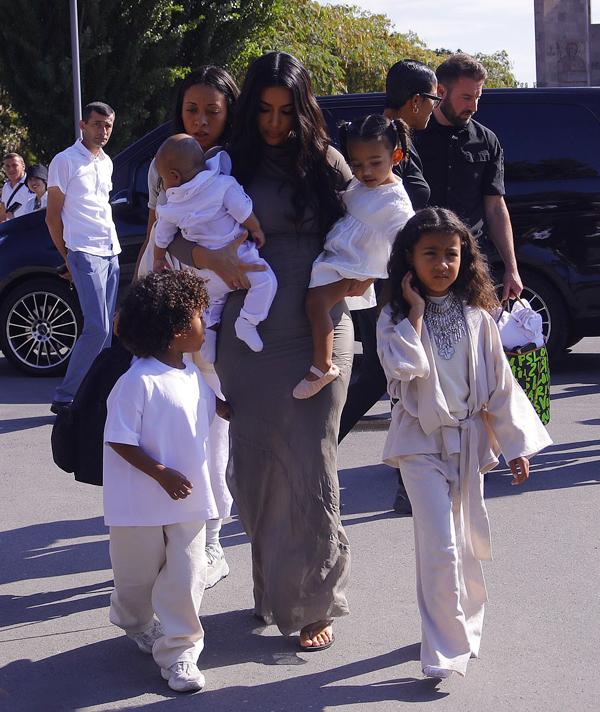 Kim hai nách bế hai con nhỏ Psalm 4 tháng tuổi và Chicago 2 tuổi. Cậu con trai Saint 3 tuổi và cô con gái cả North 6 tuổi đi sát bên mẹ tới nhà thờ.