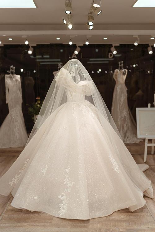 Bà tiên váy cưới Phương Linh vẫn nhớ như in lúc đó, khi nghe cô dâu nói về mong muốn, chị đã không thể rời mắt khỏi nụ cười trong sáng và vẻ đẹp như trăng rằm của cô. Cô dâu có bờ vai và cổ rất đẹp nên tôi muốn tạo điểm nhấn tôn lên ưu điểm đó - NTK đã ngay lập tức nghĩ ra chi tiết đặc biệt cho chiếc váy.