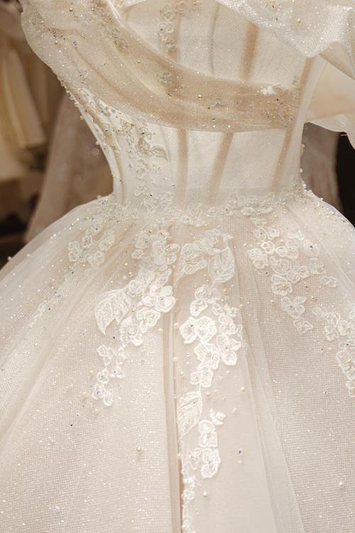 Chiếc váy được may bằng những tấm vải nhập Pháp và bắt sáng tự nhiên theo đúng tinh thần của thời trang cưới đương đại.