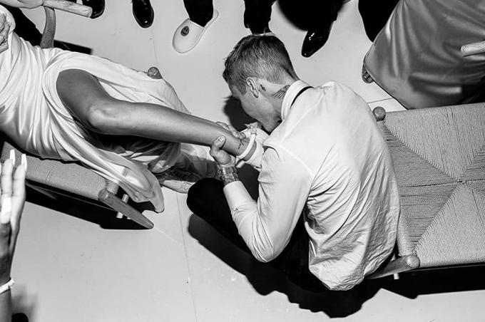 Justin Bieber kéo nịt bít tất từ trên đùi xuống cổ chân vợ để dùng răng cởi ra.