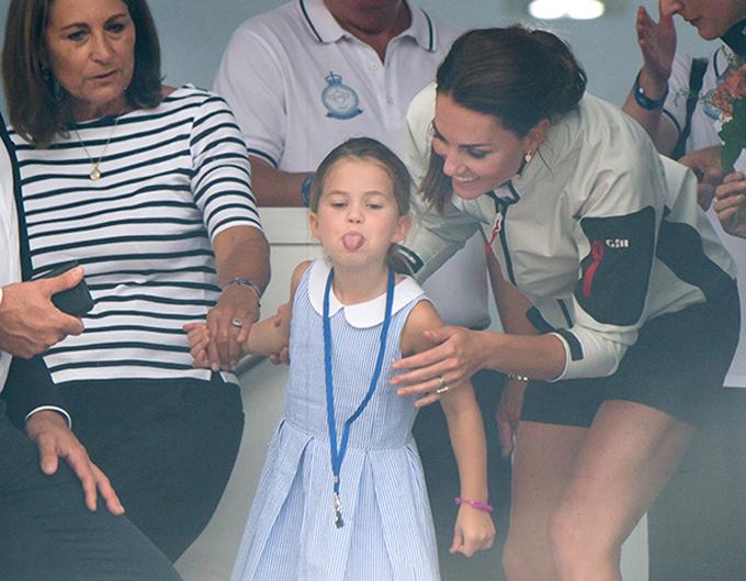 Công chúa Charlotte nắm tay bà ngoại Carole Middleton khi đi cùng bố mẹ dự lễ hội đua thuyền hồi tháng 8. Ảnh: PA.