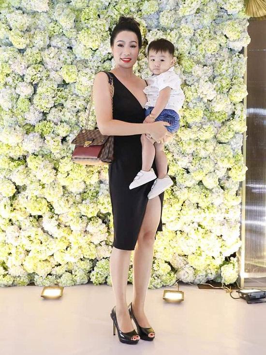 Bé Thiên Long tròn một tuổi, chào đời nhờ phương pháp mang thai hộ. Nhóc tỳ tỏ ra dạn dĩ khi được Á hậu Trịnh Kim Chi bế chụp ảnh.