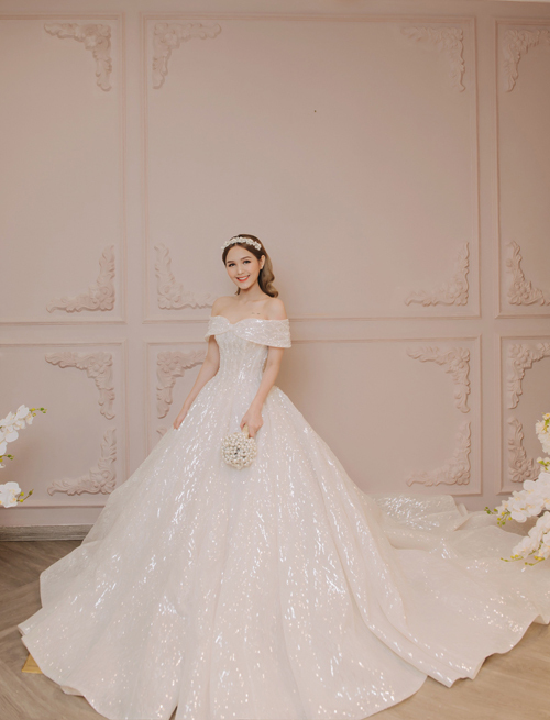 Cận kề dịp hỷ sự, cô dâu đã tìm đến NTK Linh Nga để tìm ra chiếc váy trong mơ. Bộ đầm đầu tiên mà Phạm Trang thử là thiết kế đầm xòe phồng kiểu công chúa tên Ann, có điểm nhấn tay áo trễ biến tấu từ nơ lấy cảm hứng từ váy công chúa Ann do Audrey Hepburn thủ vaitrong phim Roman Holiday. NTK khai tháchất liệu vải renPháp cao cấp kết hợp kỹ thuật corset giúp nhấn vào vòng eo con kiến của cô dâu.