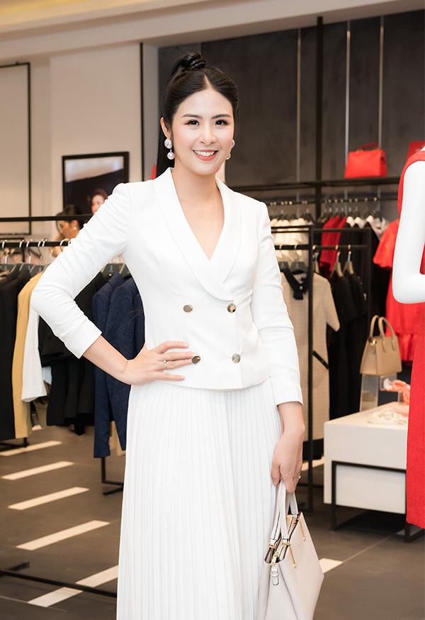 Hoa hậu Ngọc Hân khoe vẻ thanh lịch khi kết hợp vest trắng và chân váy xếp ly đồng màu.