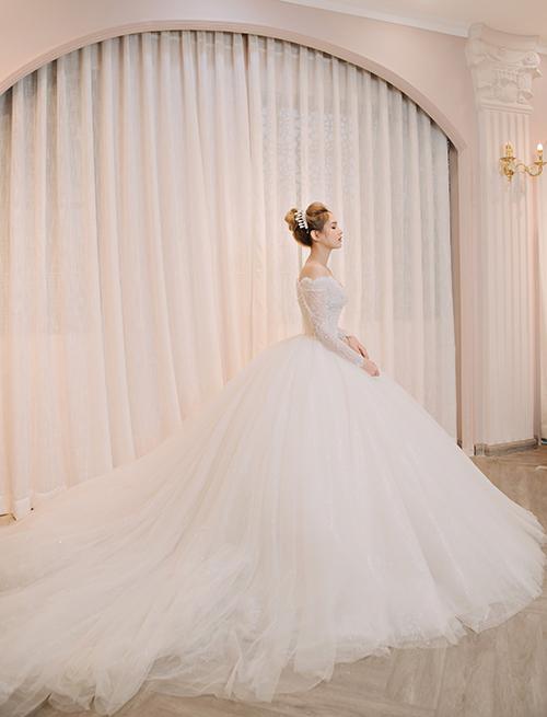 Phần đuôi váy dài xòe rộng làm từ chất liệu voan mỏng, áp dụng kỹ thuật xử lý tài tình để chiếc váy xòe nhẹ nhàng như áng mây, tạo sự thanh thoát.