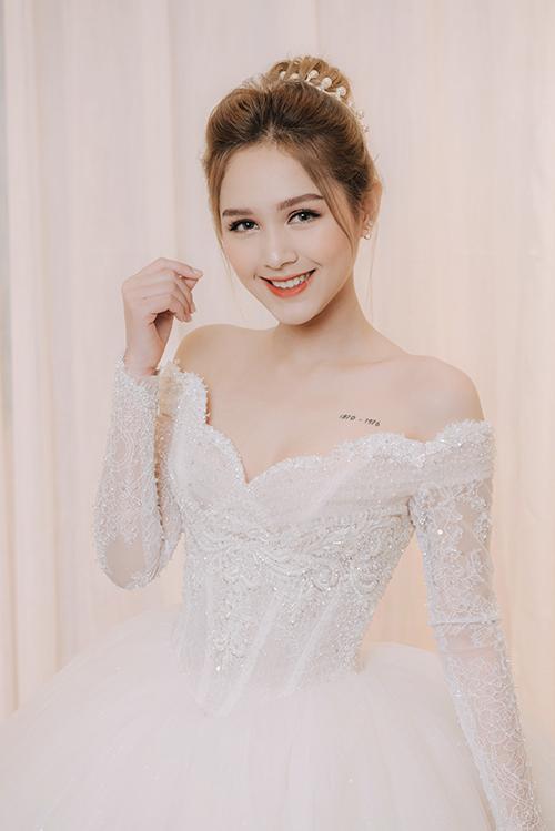 Cổ áo trễ vai tay dài được kết ngọc trai sang trọng khoe bờ vai thon. Váy được bán với giá 125 triệu đồng, giá thuê 50 triệu đồng.
