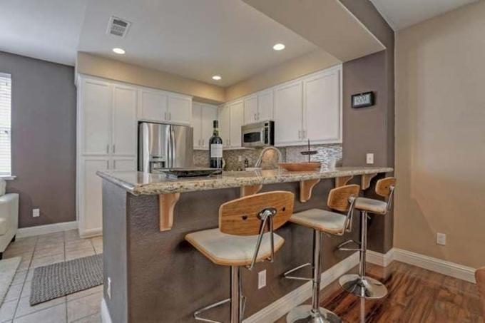 Khu vực nấu ăn kết hợp quầy bar được thiết kế theo lối tối giản, các vật dụng sắp xếp gọn gàng, ngăn nắp.