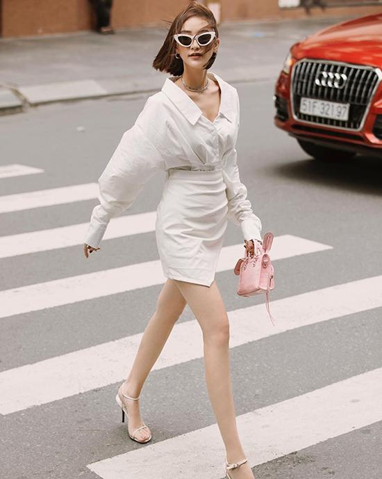 Hà Thu chọn túi hồng phấn của Balenciaga để mĩ cùng set đồ tuyền sắc trắng gồm sơ mi sệ vai, chân váy ngắn, sandal quai mảnh và kính mắt mèo.