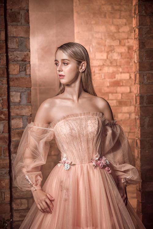 Váy trễ vai giúp cô dâu tự tin khoe nét đẹp nơi xương quai xanh, bờ vai thon. Điểm xuyết nơi vòng eo là những bông hoa nhỏ.