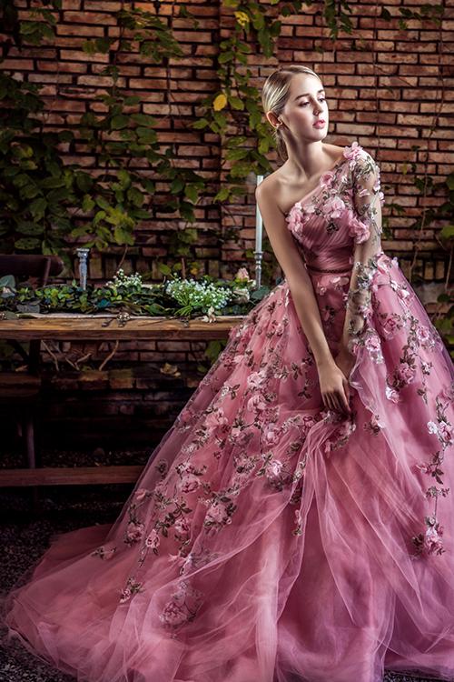 Những đóa hoa hồng leo rải rác từ cầu vai tới chân váy, tạo điểm níu giữ ánh nhìn trên trang phục.