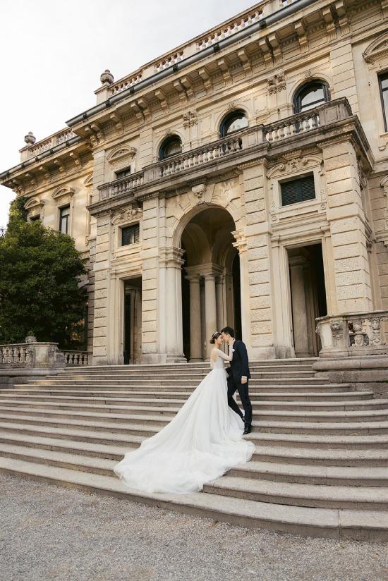 Cô dâu, chú rể chụp ảnh trước tòa lâu đài mà hai người tổ chức hôn lễ.