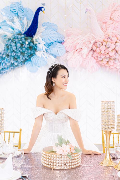 Thiết kế váy cưới đầu tiên mà Á hậu diện mang kiểu dáng trễ vai, làm lộ xương quai xanh và bờ vai thon gầy.