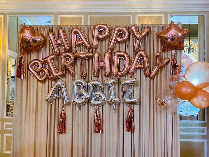 Bữa tiệc được trang trí đơn giản với bóng bay tông vàng đồng. Con gái Hoàng Anh được đặt tên Mỹ là Abbie, tên Việt Nam là Nguyễn Quỳnh Bảo Anh, tên ở nhà là Nu.