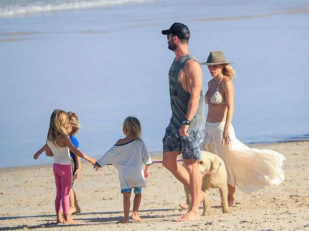 Gia đình Chris Hemsworth đi dạo trên bờ biển.
