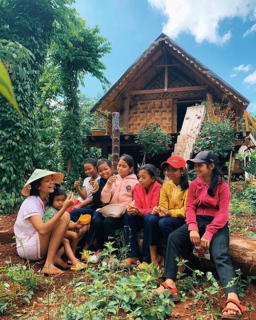 Sau khi làm vườn, HHen Niê ngồi trò chuyện cùng trẻ em trong bản làng ở quê nhà Đắk Lắk.