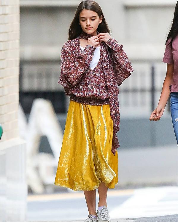 Cô bé 13 tuổi mặc chiếc áo tay cánh dơi bồng bềnh kết hợp với chân váy dài. Thả mái tóc dài, Suri duyên dáng bước trên phố như một người mẫu thời trang.