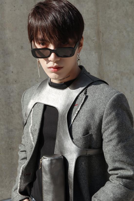 Phụ kiện ánh bạc bắt mắt được Kye sử dụng để tạo điểm nhấn cho set đồ gồm áo choàng xám ghi, thun đen và quần jeans ống rộng.