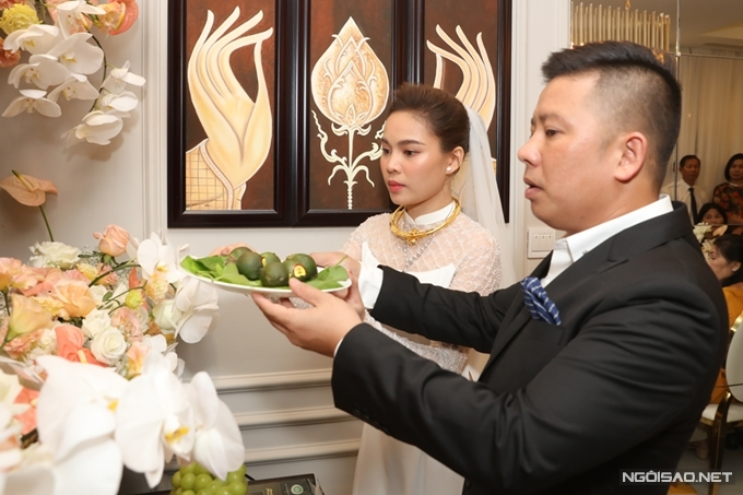 Đôi vợ chồng thắp hương và dâng trầu cau lên bàn thờ tổ tiên.