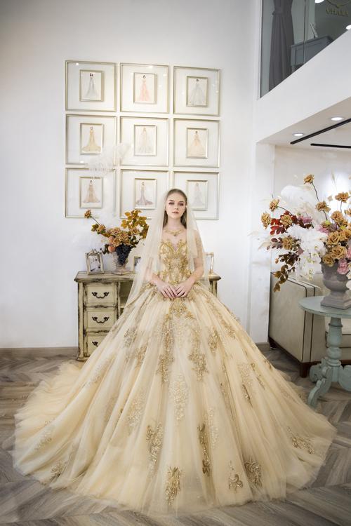 Váy cưới ngày nay không chỉ giới hạn ở gam trắng tinh khôi mà xuất hiện đa dạng các sắc màu, giúp cô dâu có thêm sự chọn lựa phù hợp cho ngày trọng đại. Bộ cánh có họa tiết, hoa văn hoàng gia rải rác dọc thân, thể hiện cá tính, gu thẩm mỹ của người diện.
