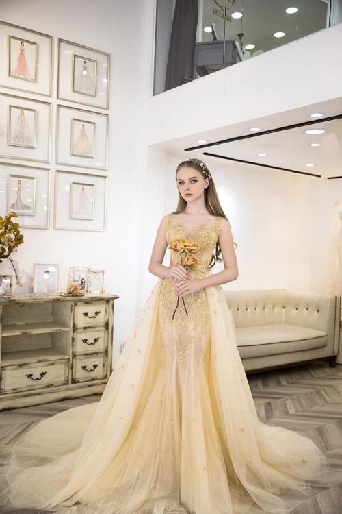 Váy cưới đuôi cá mang gam màu vàng đồng, có tà phụ gắn ngang eo, giúp từng bước đi của nàng dâu thêm lôi cuốn.