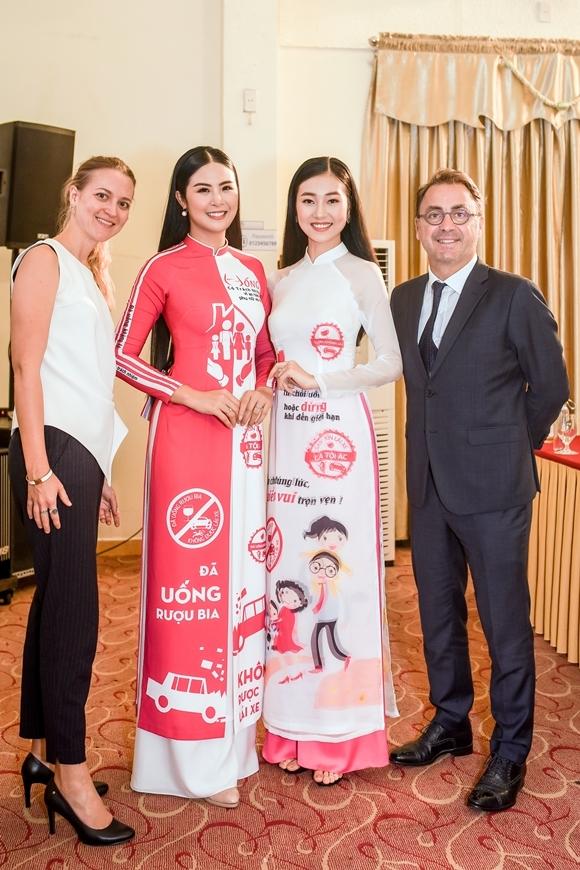 Cả hai cùng diện áo dài in họa tiết tuyên truyền an toàn giao thông do chính Ngọc Hân thiết kế, tự tin trò chuyện cùng các vị khách quốc tế.