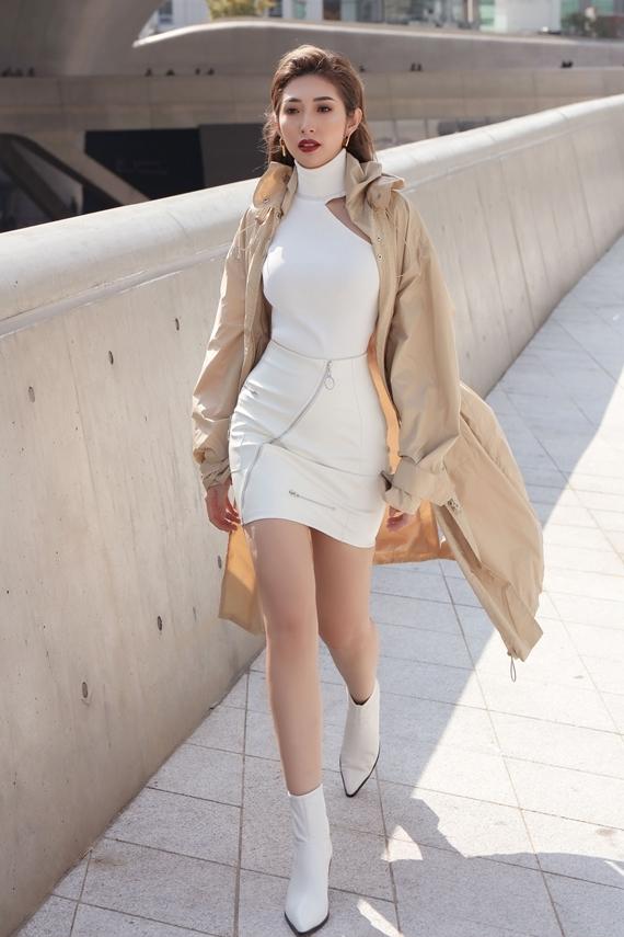 Trước đó, Khổng Tú Quỳnh xuất hiện cá tính trên đường phố Hàn Quốc với đầm cổ lọ tôn vóc dáng gợi cảm, kết hợp áo choàng dài.