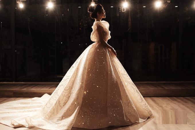 Bà tiên váy cưới Phương Linh cho biết giá trị của váy là hơn 1 tỷ đồng dù không đính bất kỳ viên kim cương nào vàdưới ánh sáng mờ ảo, chiếc váy càng tỏa sáng lộng lẫy.