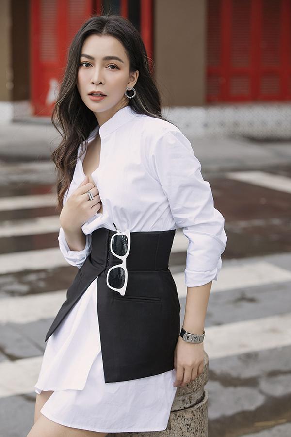 Chiếc váy trắng dáng sơ mi trở nên sinh độnghơn khi kết hợp với đai eo màu đen lấy cảm hứng từ thiết kế của áo vest. Đây cũng là điểm nhấn của toàn bộ set đồ.