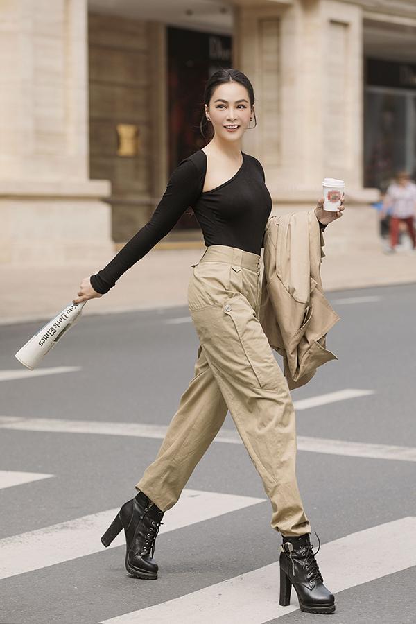 Cô hoàn toàn thoát khỏi hình ảnh điệu đà của những ngày đến công sở bằng cách kết hợp quần baggy đai cao, áo phông lệch mai và boot thấp cổ hầm hố.