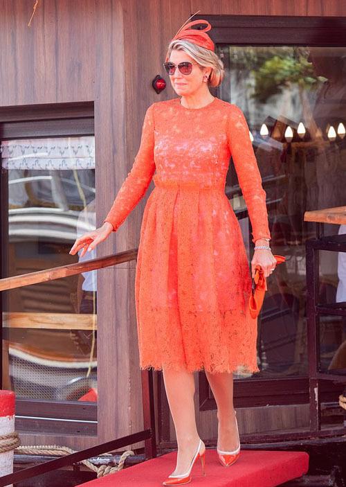 Hoàng hậu Maxima nổi bật khi diện nguyên một bộ đồ màu cam, bao gồm váy, mũ đội đầu, ví cầm tay và giày cao gót đều cùng tông màu này. Đây được xem là màu truyền thống của hoàng gia Hà Lan. Bà kết hợp thêm cặp kính mát giữa thời tiết khá nóng nực ở Ấn Độ.