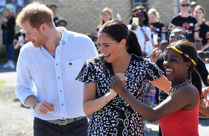 Vợ chồng Harry vui vẻ nhảy cùng người dân địa phương trong chuyến công du châu Phi hồi tháng trước. Ảnh: Reuters.