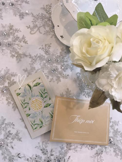 Thiệp cưới của cặp vợ chồng được trang trí bởi hình vẽ màu nước, có tông trắng và vàng đồng chủ đạo, mang nét thanh lịch.