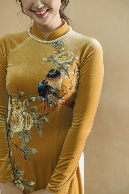 Vẻ đẹp thanh xuân của cô dâu Ngọc Linh được tôn nhờ bộ áo dài vàng rực rỡ. Họa tiết đôi chim uyên ương quấn quít, hoa thêu tay rực rỡ, đâm chồi nảy lộc cũng là lời chúcmà Ngọc Hân gửi gắm tới đàn em thân thiết, rằng cuộc sống sắp tới của uyên ương sẽ luôn gắn kết, hạnh phúc.Bộ ảnh được thực hiện bởi áo dài: Ngọc Hân Boutique, váy cưới: Hacchic Couture.