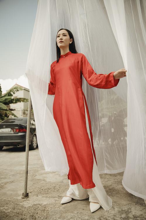 Áo dài nữ có dáng thụng, cổ trụ thấp, phần cổ áo được điểm một hạt ngọc làm điểm nhấn.