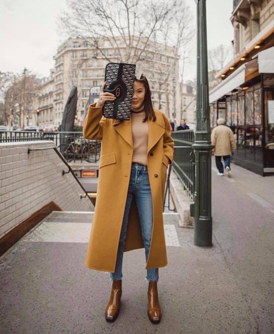 Set đồ dạo phố hay đến văn phòng đậm chất thu đông với áo dệt kim tông beige, áo khoác vàng mù tạt đồng điệu bốt da bóng và quần jeans ống ôm.