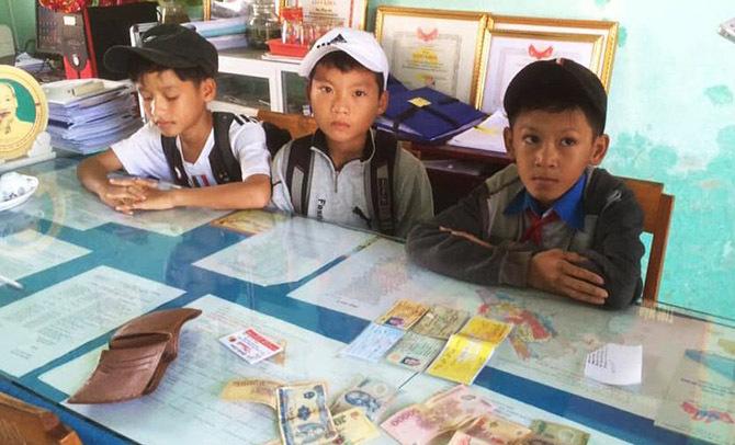 Ba học sinh mang chiếc ví nhặt được đến UBND xã bàn giao. Ảnh: Đại Hiệp.