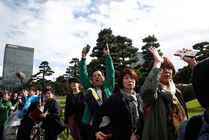 Người dân xếp hàng và hô to Banzai (Vạn tuế!) để mừng lễ đăng quang của Nhật hoàng bên ngoài cung điện ở Tokyo. Ảnh: Reuters.