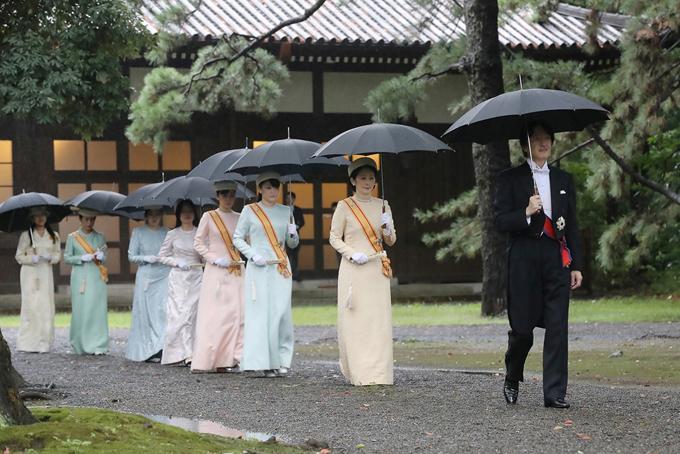 Thái tử Akishino vàThái tử phi Kiko (đi đầu hàng), hai con gái của Nhật hoàngNaruhitocùng các thành viên khác của hoàng gia che dùtiến về nơi làm lễ dưới trời mưa. Ảnh: Japan times.