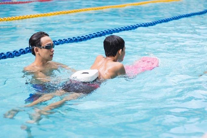 Cựu vận động viên bơi lội tranh thủ vận động trong lúc dạy bơi cho các em nhỏ vào sáng cuối tuần.