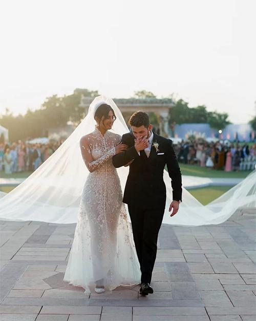 Hoa hậu Thế giới năm 2000 - Priyanka ChopraHoa hậu Priyanka Chopra đã diện váy ren quyến rũ, tinh tế và đội chiếc khăn voan dài tới 23 m, được nâng bởi 5 người đàn ông, đến từ NTK Ralph Lauren. Váy cưới của Priyanka một ngoại lệ đặc biệt vì suốt 50 năm sự nghiệp, Ralph Lauren mới chỉ thiết kế 3 chiếc váy cưới cho người trong nhà gồm con gái, con dâu và cháu gái ông. Cô dâu, NTK Lauren và stylist Mimi Cuttrell đã mất nhiều ngày liền để thống nhất về bản phác thảo váy cưới thêu ren, cổ cao. Đặc biệt, ẩn sau những lớp vải lụa là những thông điệp ý nghĩa về tình cảm gia đình. NTK đã khâu vào trong bộ đầm một mảnh vải từ váy cưới của mẹ Nick từ năm 1985 và thêu các dòng chữ: Nicholas Jerry Jonas - tên đầy đủ của chú rể, 1/12/2018 - ngày cưới của uyên ương, Madhu & Ashok (tên của bố mẹ Chopra), Om Namah Shivay (một câu nói trong đạo Hindu), cụm từ Gia đình, Hy vọng, Bao dung và Tình yêu. Để thực hiện bộ váy, nhà mốt đã tốn 1.826 giờ thực hiện, đính kết hơn 2 triệu hạt cườm ngọc trai, hàng nghìn viên pha lê Swarovski. Chú rể Nick Jonas cũng mặc vest của Ralph Lauren.Mặt khác, ngoài cô dâu chú rể, 12 phù rể, 12 phù dâu, 4 cô gái rải hoa dọc lễ đường và một người mang nhẫn đều diện thiết kế của nhà mốt Ralph Lauren.