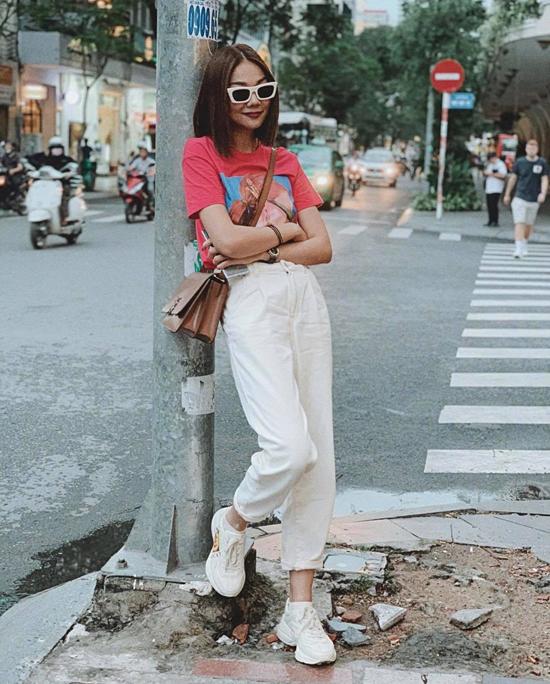Khi vừa xuống tóc, Thanh Hằng chọn ngay áo thun tông hồng để giúp hình ảnh của cô thêm phần trẻ trung. Phối hợp cùng mẫu áo bắt mắt là quần jeans xắn gấu, giầy Gucci đế thô và túi đeo chéo củaBurberry.