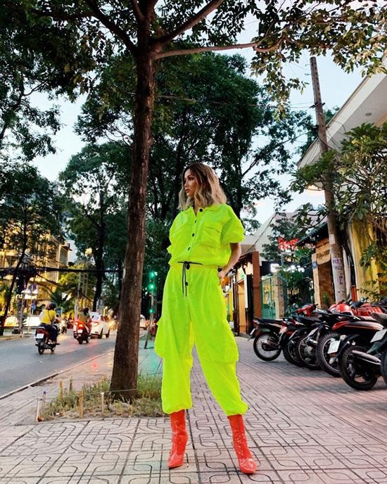 Hoa hậu HHen Niê nổi bật trên phố khi diện nguyên set đồ xanh neon đi kèm bốt da bóng tông cam.