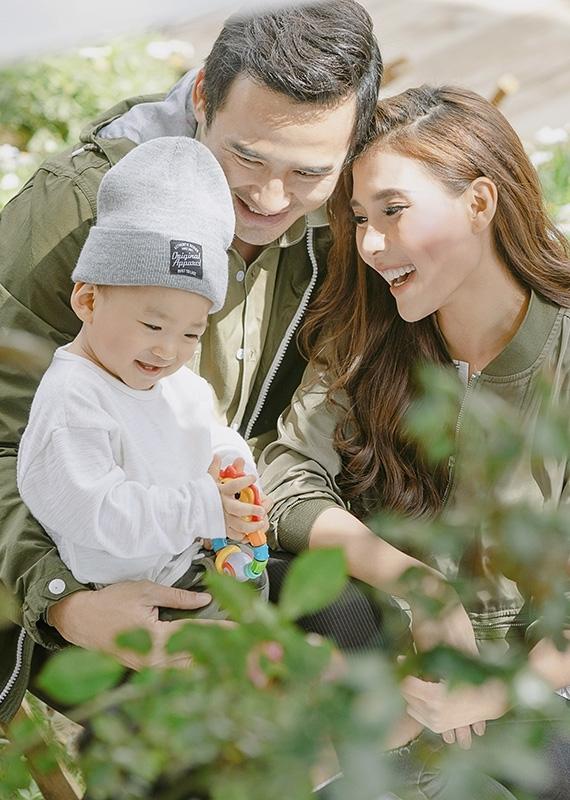 Nhóc tỳ cười tít mắt khi vui đùa bên bố mẹ trong không gian thiên nhiên thoáng đãng.